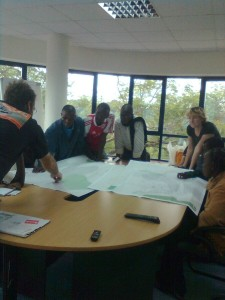 Map Kibera team reviews printed map (in draft stages) of their work